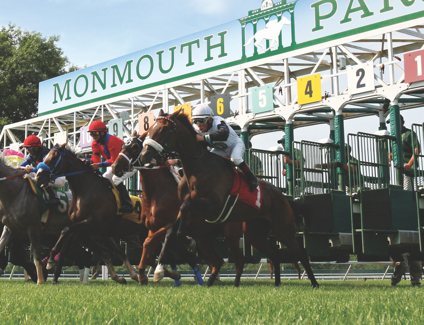 Horses racing in front of Monmouth Park sign